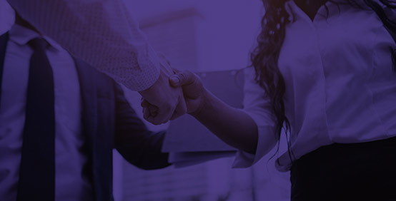 Man and woman shaking hands to enter into a reseller relationship with Kaplan's Reseller Partner Program