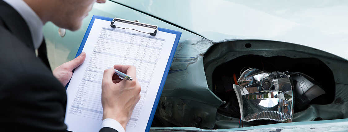 Claims adjuster reviewing damage to a vehicle