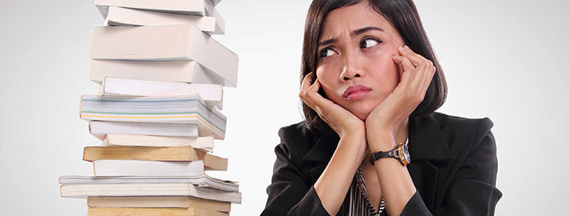 Anxious woman staring at a pile of books as she prepares to study for a securities exam