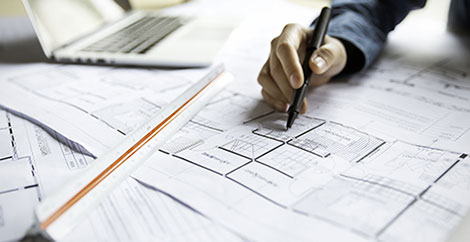 Person drawing on architectural plans with pen image