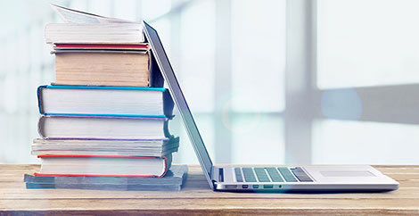 Stack of reference books with an open laptop leaning against them image