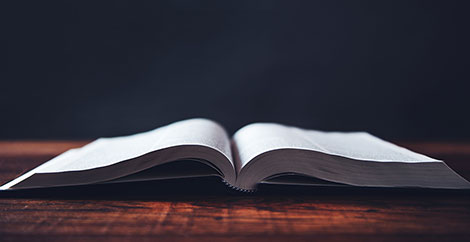 Open hardcover textbook on a wood table image