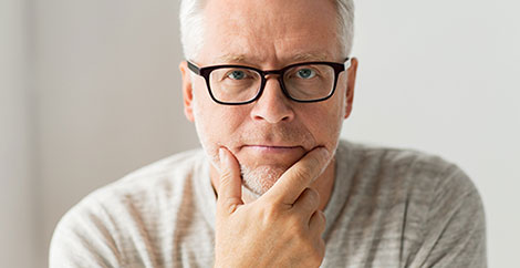 Man with glasses in white shirt sitting with hand on chin image