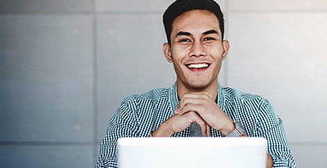 Smiling man with green checked shirt sitting in front of an open laptop image