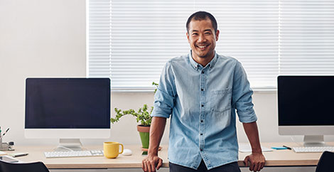Man leaning against a desk with multiple computer monitors image