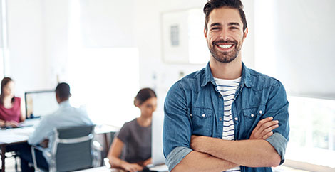 Man in denim shirt in office standing in front of colleagues working at their desks image