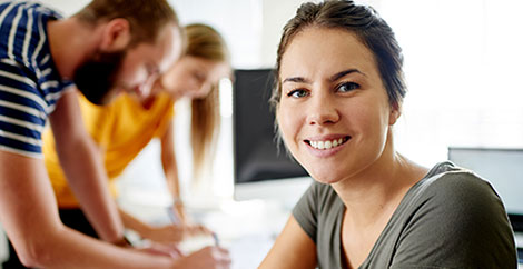 Woman sitting at conference table with colleagues working next to her image
