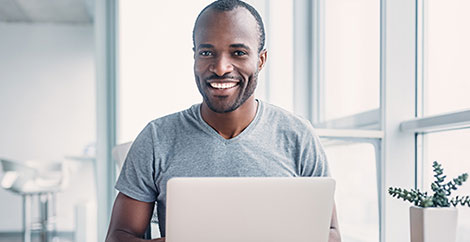 Man in grey t shirt sitting in front of open laptop image