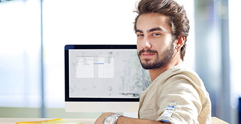 Man in tan shirt sitting turned away from a computer monitor image