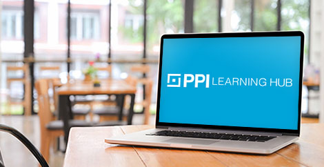Laptop with PPI Learning Hub logo on screen on a table in a coffee shop image