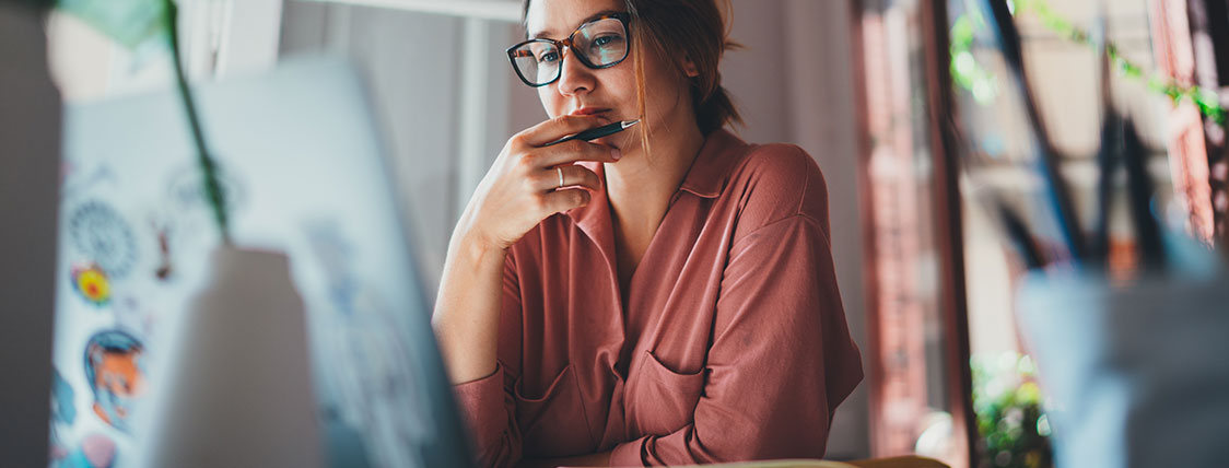 Woman sitting at desk looking at computer monitor image