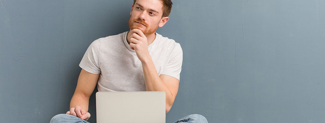 Man with quizzical expression sitting with laptop in his lap and hand on his chin image