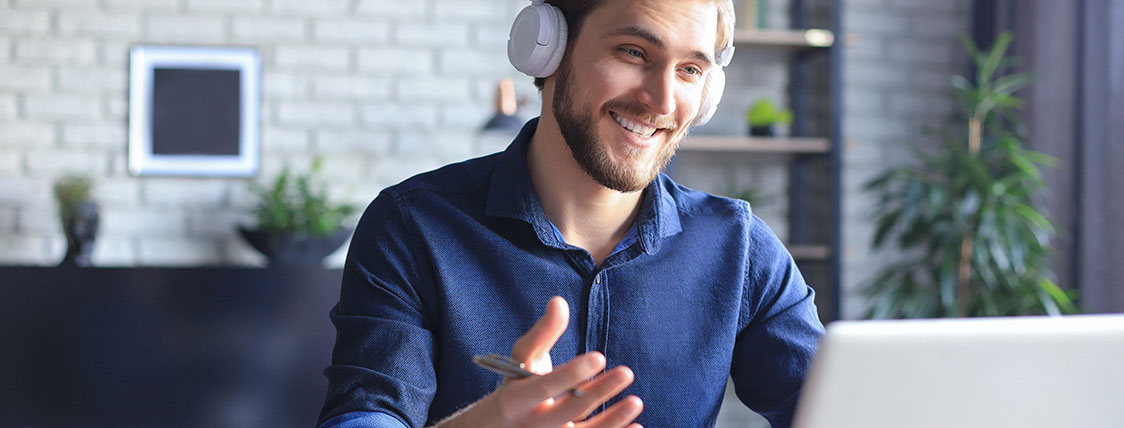 Man wearing headphones and sitting in front of an open laptop image