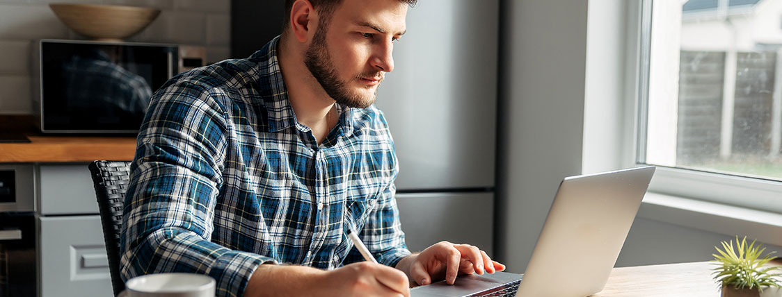 Man sitting at a desk looking at a laptop image
