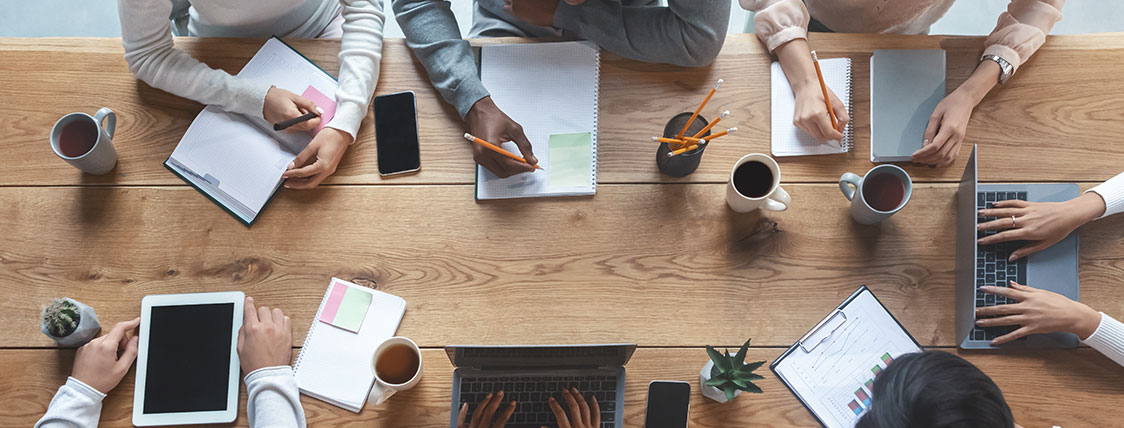 Top down view of multiple colleagues working together at a conference table image
