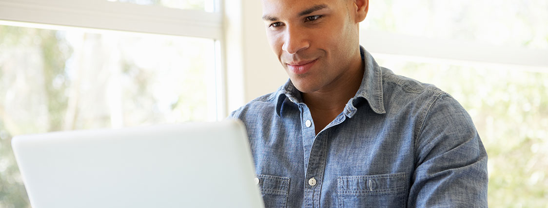 Man in denim shirt working on a laptop in front of a window image