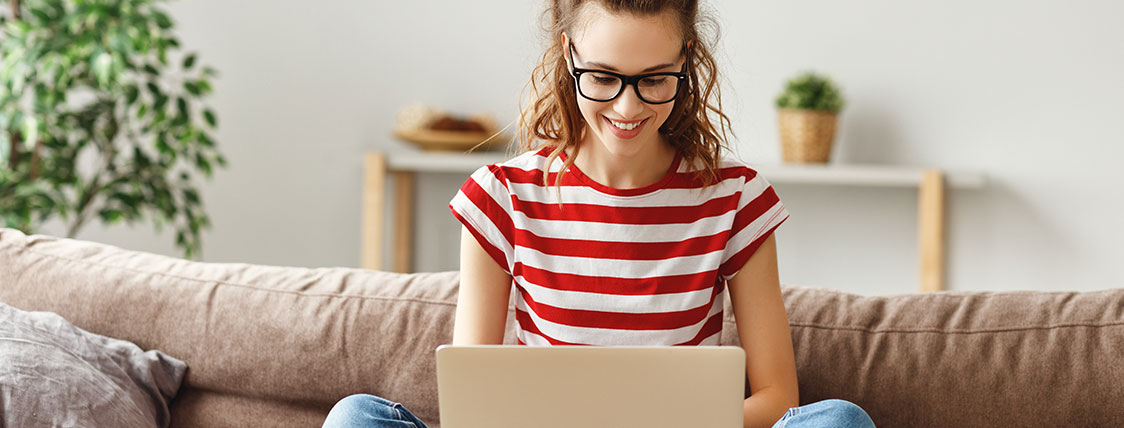 Woman seated on a sofa working on a laptop image