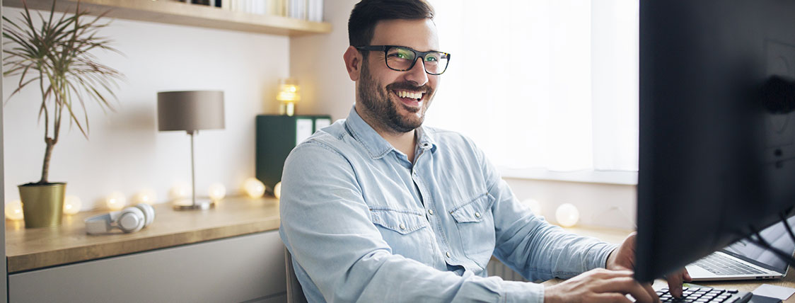 Man sitting at desk in office in front of computer monitor image