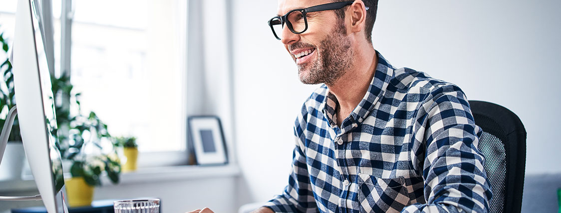 Man in plaid shirt working on a computer at a desk with a monitor image