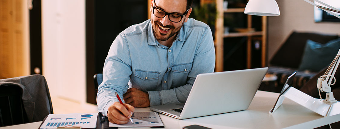Man sitting at desk in office with a laptop taking notes image