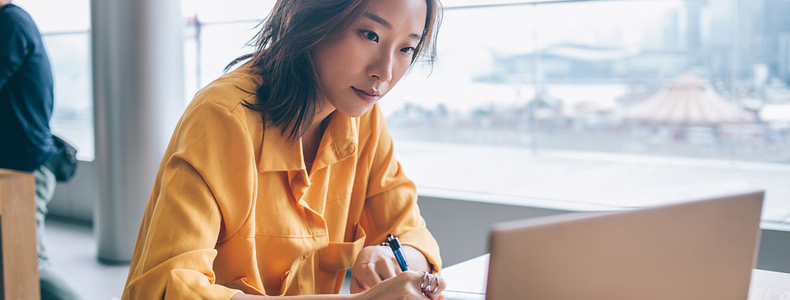 Woman sitting at table in front of window working on a laptop image