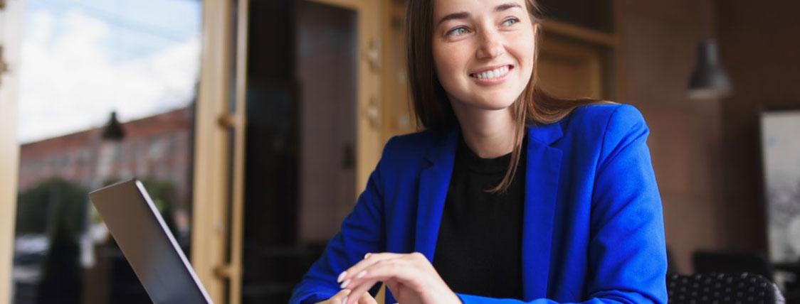 Woman in blue blazer working on a laptop in an office image