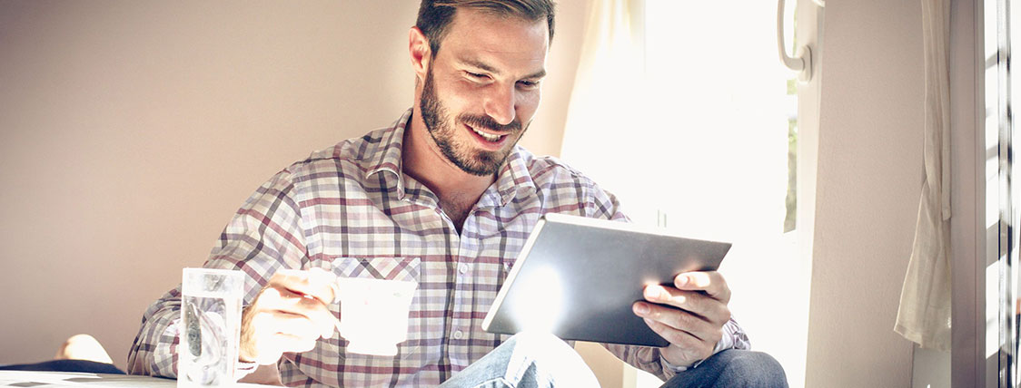 Man sitting holding a coffee cup and a tablet device image