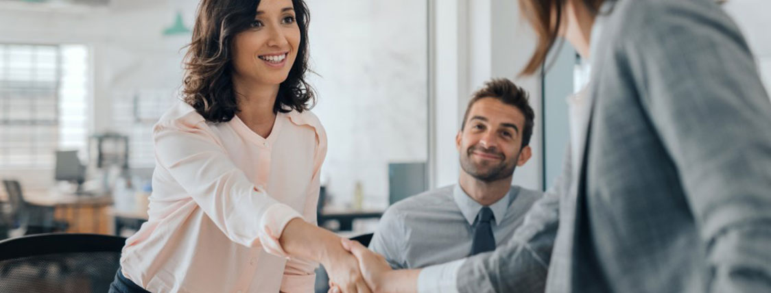 Two people shaking hands in an office with another colleague looking on image