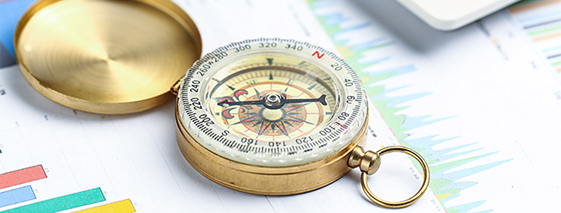 Compass on financial papers indicating a decision - CFA Charter versus FINRA Series 7