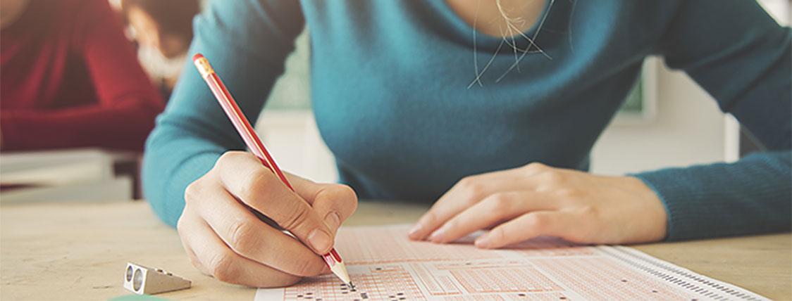 Woman sitting for a CFA mock exam to prepare for the CFA Program exam