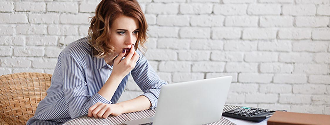 Woman looking at her CFA Exam results on her laptop