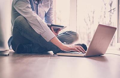 Man sitting on the floor attending an online class on a laptop.
